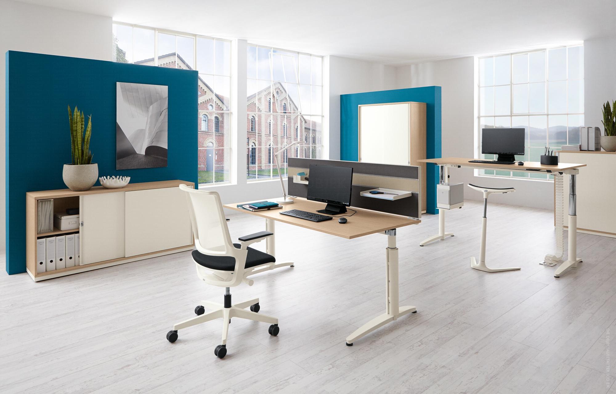 Offene Bürofläche mit elektrisch höhenverstellbaren Tischen, ergonomischen Bürostühlen und ergänzender Möblierung.