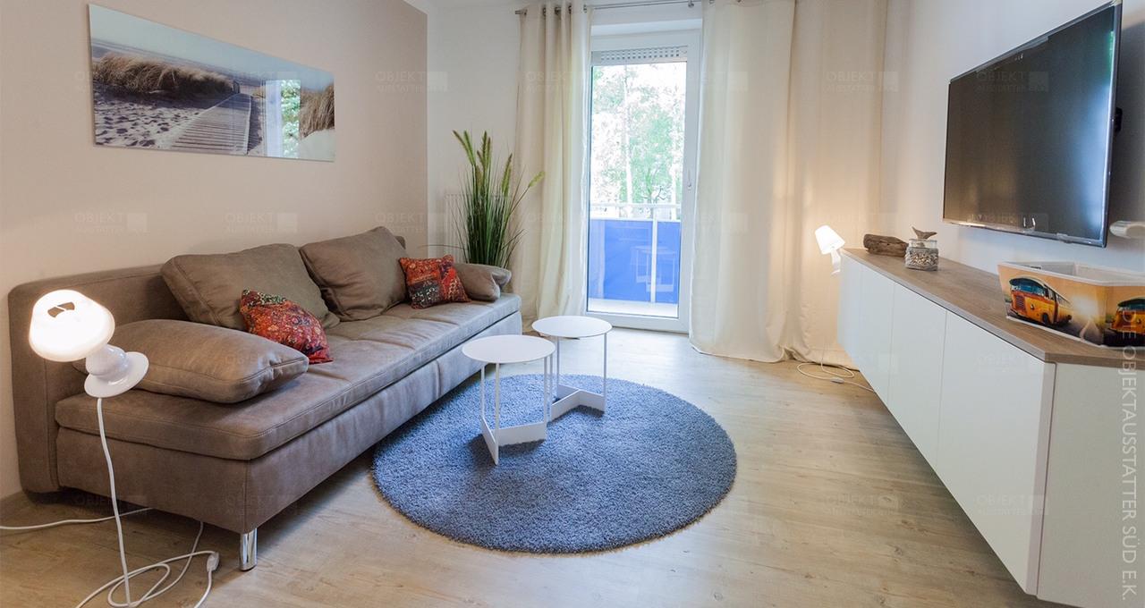 Objekteinrichtung Wohnfläche mit Sofa, Couchtisch, Beleuchtung, TV-Möbel und Fernsehgerät.