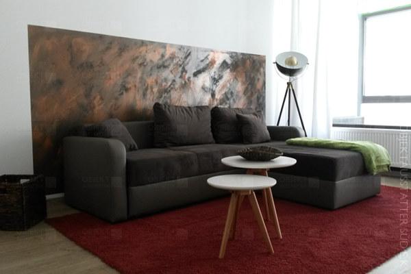 Wohnlandschaft aus Couch mit Kanapee, Beistelltischen, Stehlampe und Teppich.