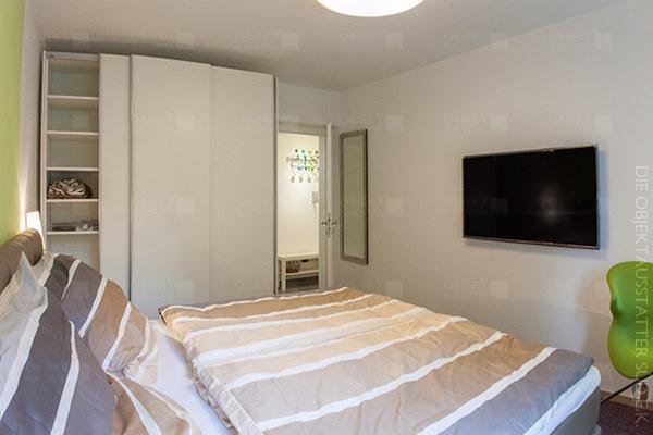Schlafzimmer mit Bett, Kleiderschrank, Fernsehgerät und Loungestuhl.