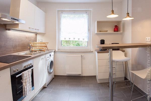 Einbauküche mit Herd, Cerankochfeld, Spülmaschine, Waschmaschine sowie Essbereich und passender Beleuchtungslösung.