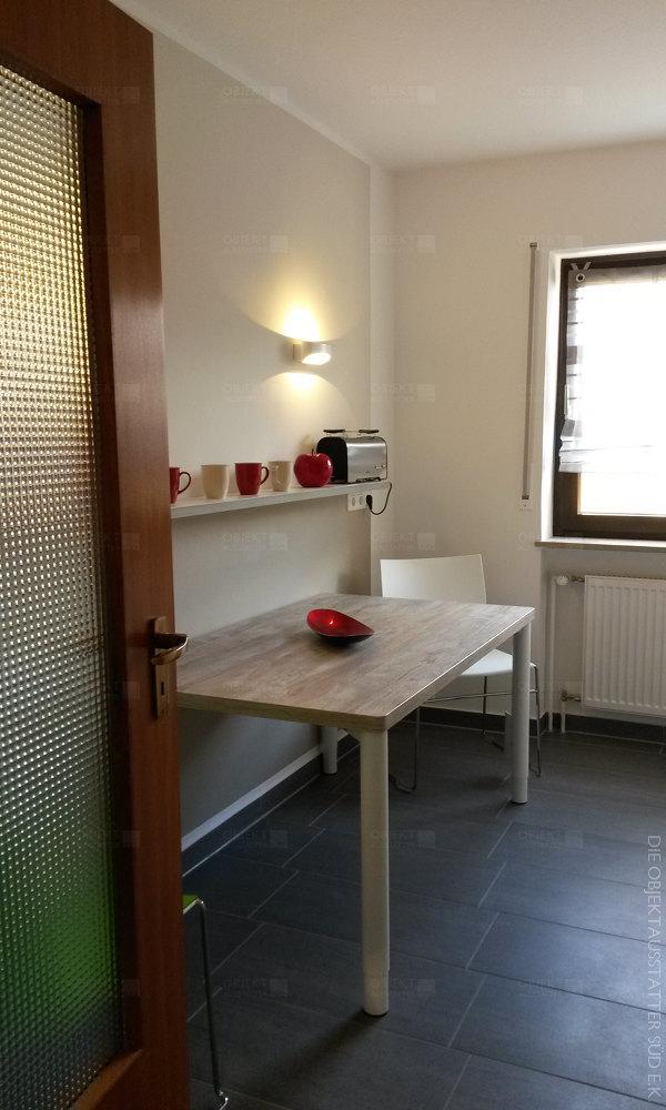 Essbereich mit Esstisch, Esszimmerstühlen und abgestimmerter Beleuchtung.